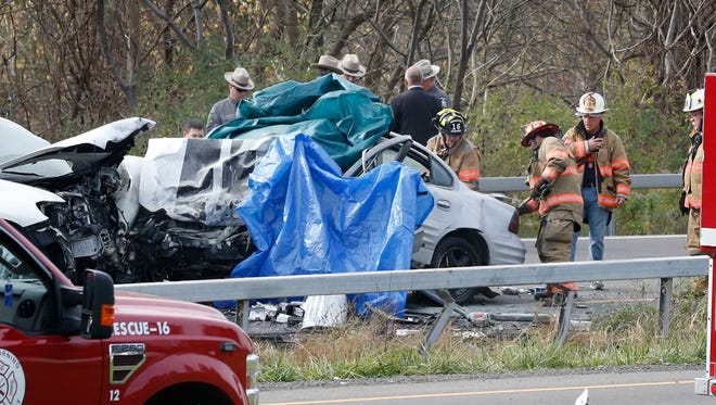 East Corning fire crews open the trunk of a sedan that police say crossed the median on State Route 352 and collided with another vehicle in Corning on Nov. 2. The driver was pronounced dead on scene.
