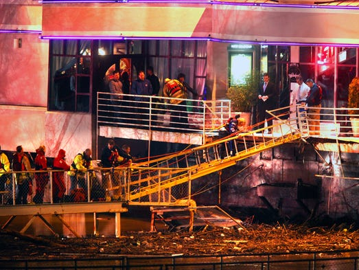 March 12, 2011: A woman walks down a fire ladder, used as an improvised ramp, during a rescue operation in which customers were off-loaded from Jeff Ruby's Waterfront in Covington after the floating restaurant's moorings broke loose. Swift currents took the high-end restaurant about 100 feet down the Ohio River in Covington until it became lodged under the Clay Wade Bailey Bridge.