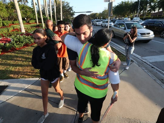 A crossing guard hugs a student as he walks to Marjory Stoneman Douglas High School for the first day of school since the shooting Wednesday, Feb. 28, 2018.