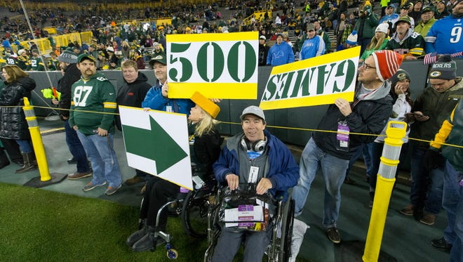 Brian Gushue (center) was able to get on the field before the Green Bay Packers game against the Detroit Lions Monday at Lambeau Field. His friends made signs to celebrate that this was Brian's 500th NFL game, despite the San Diego man's challenge of having cerebral palsy.