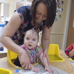Becca Huffman, program director at Rosebrook Child Development Center in Brighton, helps 8-month-old Fiona Steffens use her hands to apply paint to an art project.