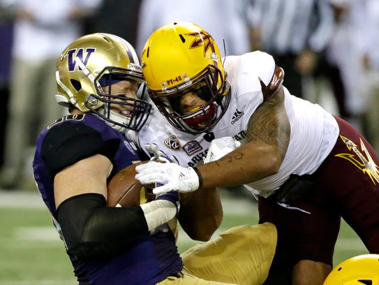 Washington tight end Will Dissly takes a hit from Arizona
