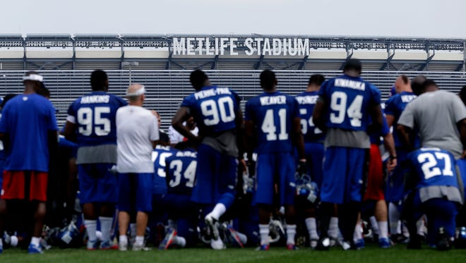 The New York Giants huddle in front of MetLife Stadium during a NFL football camp in East Rutherford, N.J., Tuesday, July 22, 2014. The stadium was presented with the 2014 Facility of Merit for Safety and Security Award.