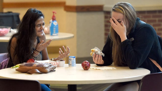 Ivy Tech students Manali Prajapati (left) and Mackenzie Harger of Newburgh share a laugh while eating free breakfast during the first day of classes at Ivy Tech Community College Southwest in Evansville Tuesday.