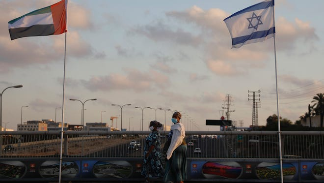 Women wearing face masks against the coronavirus walk past United Arab Emirates and Israeli flags at the Peace Bridge Sunday in Netanya, Israel.