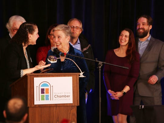 Pat Convery, president of the Howell Area Chamber of Commerce, accepts this year's Citizen of the Year award from last year's awardee, Patti Griffith, as her family looks on at the Chamber's annual awards dinner Thursday, Jan. 25, 2018