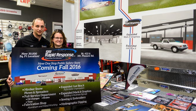 Mark and Melissa Sallada pose for a picture with their proposed new building they hope to break ground for in April 2016 as 911 Rapid Response held an open house on Monday, December 14, 2015 to unveil their new location and building they hope to break ground for in April 2016.