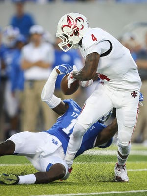 Louisiana-Lafayette wide receiver Jamal Robinson (4) has the ball stripped by Kentucky cornerback J.D. Harmon, which resulted in a turnover, during the first half of an NCAA college football game in Lexington, Ky., Saturday, Sept. 5, 2015. (AP Photo/David Stephenson)