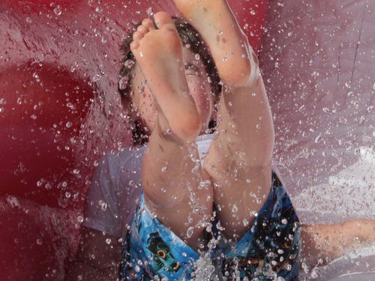 Mamie Youngblood on the waterslide with feet in the air.