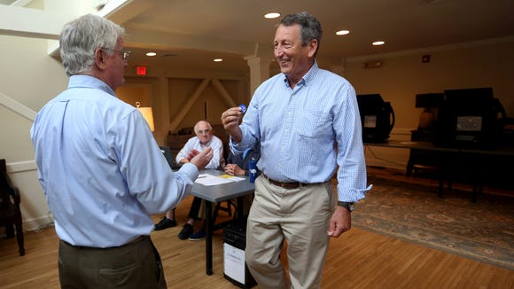 Poll volunteer Tom Spain hands out stickers to Rep. Mark Sanford after he cast his own ballot at Alhambra Hall polling station Tuesday, June 12, 2018, in Mt. Pleasant, S.C.