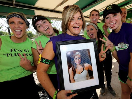 Maria Filorimo holds a picture of her daughter Taylor Filorimo, who lost a 3 year battle with of cancer 2 years ago as she stands next to her daughter Skylar Filorimo as they are surrounded by members of the Fury 97 softball team, on Saturday, September 6, 2014, at the Play 4 Tay Tournament at Barfield Crescent  Park. Taylor Filorimo always loved to take funny pictures so the group made funny faces in honor of Taylor Filorimo during this picture. The Fury players L to R Kaylee Rock, Jordan Spicer, Baylee Cook, Hannah Bodenhorn, and Jordan Fortel.