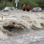 Rescue workers stand between two cars caught in a flash  flood,  with motorists trapped inside, on Indian Bend Road between Scottsdale and Hayden roads on Aug. 24, 2006.