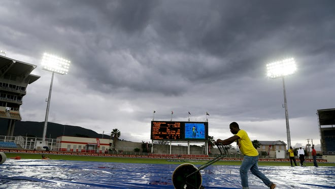 Ground staff dry the wicket under a stormy sky as rain delays day three of the second cricket Test match between India and West Indies at the Sabina Park Cricket Ground in Kingston, Jamaica, Monday, Aug. 1, 2016. The Jamaica Meteorological Service advised small vessels to return to shore as a storm moves west from Hispaniola with strong winds and heavy.