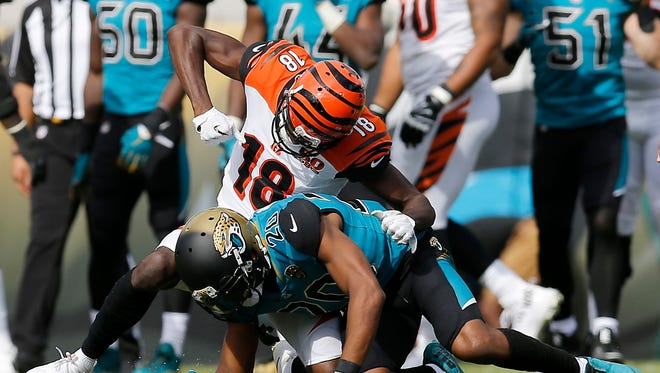 Bengals wide receiver A.J. Green (18) throws a punch at the helmet of Jaguars cornerback Jalen Ramsey (20) after pulling him to the ground after a play in the second quarter Sunday.