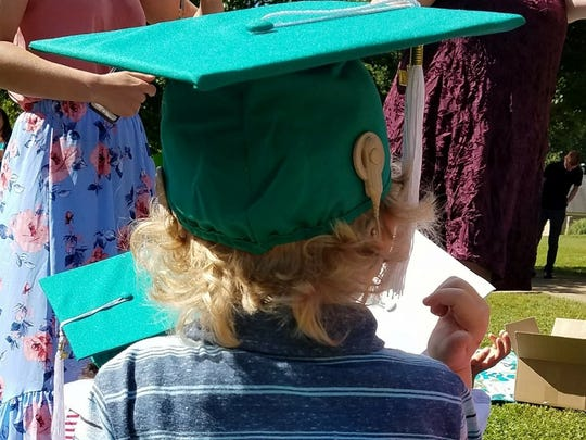 Indy Mueller wears his cochlear implant on the outside of his pre-school graduation cap. Indy was born profoundly deaf and received cochlear implants at the age of 11 months.