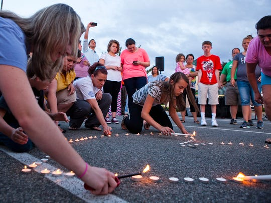 Community members light a heart-shaped ring of candles during a prayer vigil organized by Vitalize Church in Hardy, Va. for the victims of the shooting captured live on WDBJ7 earlier that day just a few miles away on Wednesday, Aug. 26, 2015.