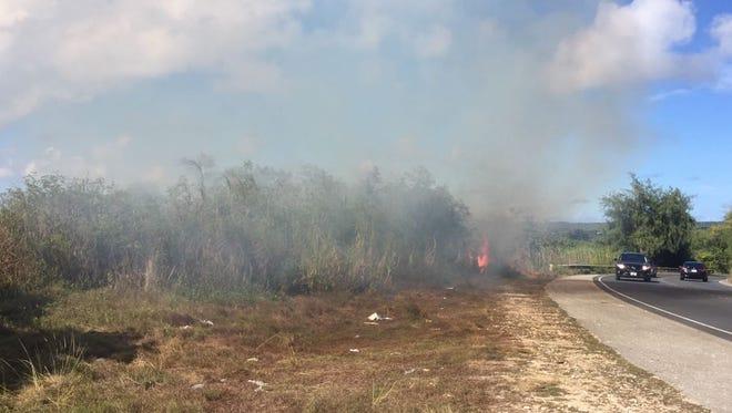 A grass fire burns along Alageta Street, near the Barrigada overpass, Friday afternoon.