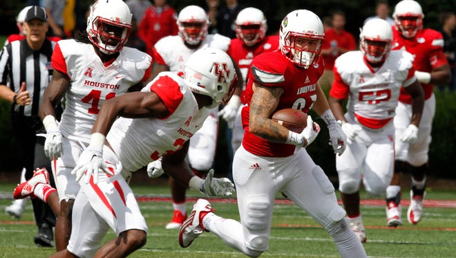 University of Louisville's Micky Crum (83) fights to break free from University of Houston's William Jackson (3) during the second half of play at Papa John's Stadium in Louisville, Kentucky.       September 12, 2015