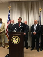 U.S. Attorney Mike Hurst, flanked by officials from