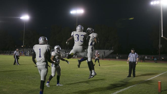 Cesar Chavez's Pavone Meyers (33) and Dominic Yanez (6) celebrate a touchdown against Alhambra at Alhambra High School in Phoenix, AZ on Sept. 11, 2015.