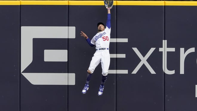 Los Angeles Dodgers right fielder Mookie Betts robs Atlanta Braves' Marcell Ozuna of a home run during the fifth inning of Game 6 on Saturday.