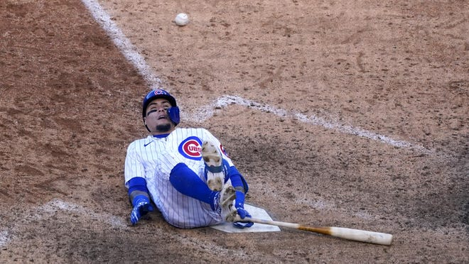Chicago Cubs shortstop Javier Baez falls after fouling off a ball during the ninth inning in Game 2 of the National League wild-card series against the Miami Marlins on Friday, in Chicago.
