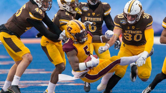 Central Michigan defensive back Devonni Reed (5) gets upended by the Wyoming defense during the Famous Idaho Potato Bowl on Friday, Dec. 22, 2017, in Boise, Idaho.