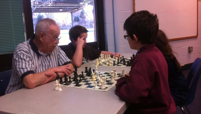 Foster Grandparent Ben Gonzalez plays a game of chess with students at the Boys & Girls Club where he volunteers.