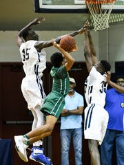 Lahat Thioune (right) helps defend in a playoff game last season against Central Florida Christian Academy.