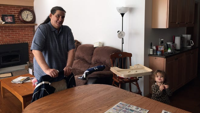Chris Chronister with his granddaughter Zoeyin the living room of the family's house, rebuilt after a fire a year ago.