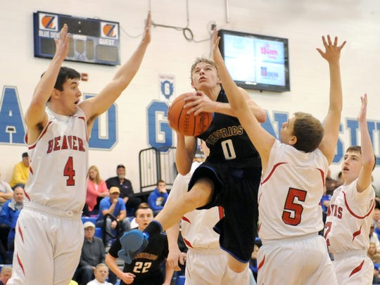 Philo's Wyatt Carder leaps toward the basket between Lisbon Beaver defenders Hayden Grafton (4) and Christian Cooper a Division II boys sectional tournament first-round game Wednesday at Zanesville High School.