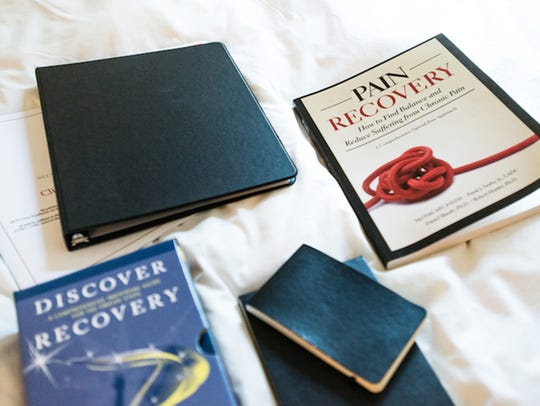 Books about recovering from pain sit on patient John