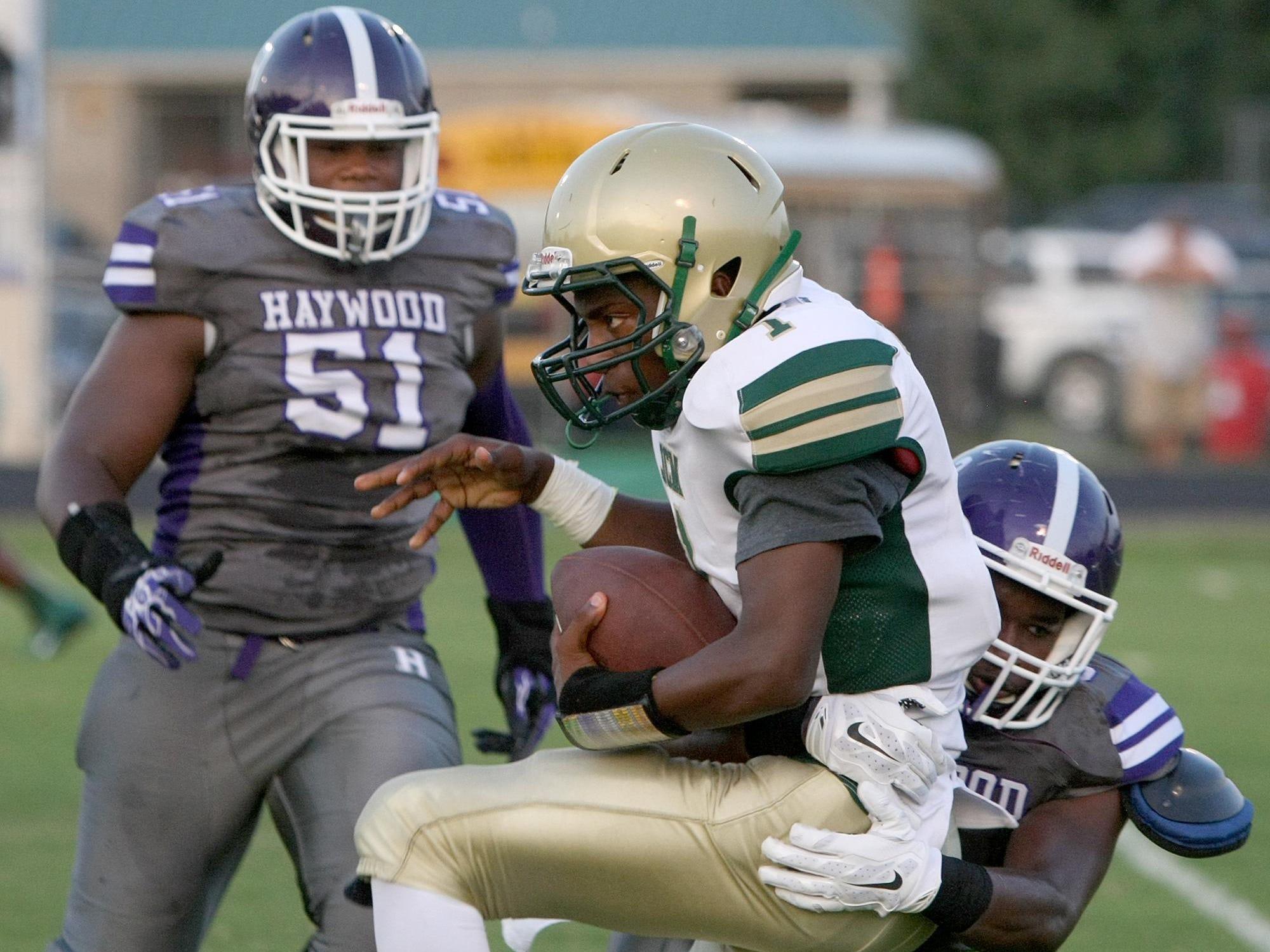 JCM quarterback Adryan Grundy is hit by Haywood linebacker Jaleel Turner at John B. Hooper Memorial Stadium in Brownsville on Aug. 29.