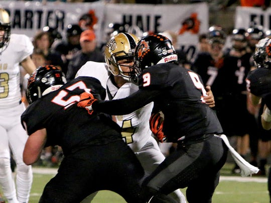 Rider's Nick Thomas (center) sheds a block by Aledo's Seth Strickland (57) to tackle running back Jase McClellan (9). Aledo eliminated Rider from the playoffs and play Corpus Christi Calallen for the Class 5A Division II state title Friday.