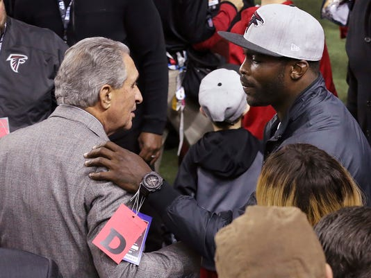 Former Atlanta Falcons quarterback Michael Vick, right, and team owner Arthur Blank greet each other and exchange hugs on the sideline before the Falcons played the New Orleans Saints in an NFL football game Sunday, Jan. 1, 2017, in Atlanta. (Curtis Compton/Atlanta Journal-Constitution via AP)