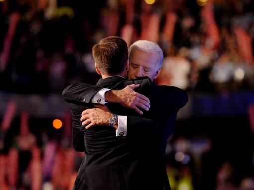 Vice presidential candidate Joe Biden hugs his son
