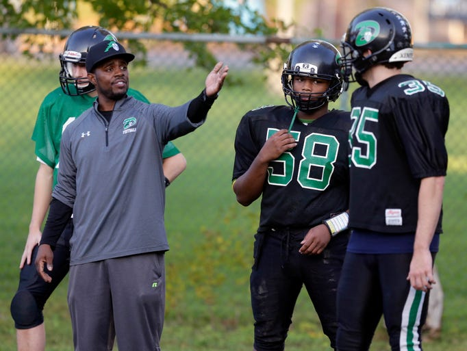 Football coach Quincy LaGrant talks with the team during