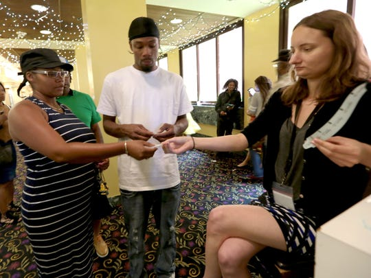 Shawana Nimox and her husband Derrell Nimox get their number from Wayne County intern Elizabeth Raczkowski to wait and pay their 2013 back taxes as the deadline approached on June 30, 2016.