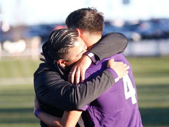 New Rochelle coach Jarohan Garcia hugs player Marcos