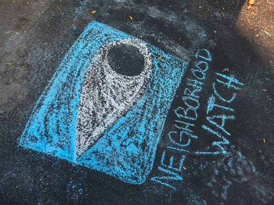 A neighborhood watch logo drawn in chalk marks the spot for a National Night Out gathering Tuesday, Aug. 1, in St. Cloud.