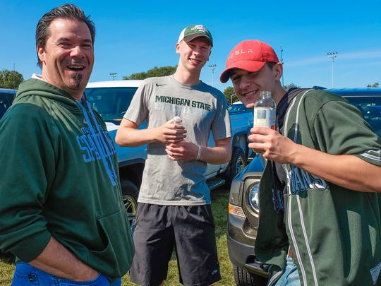 Rick Chrisman, left, and MSU students Chase Garland and Caleb Chrisman have fun tailgating at Munn Field, which is designated as a no alcohol zone before the game on Saturday, Sept. 2, 2017.