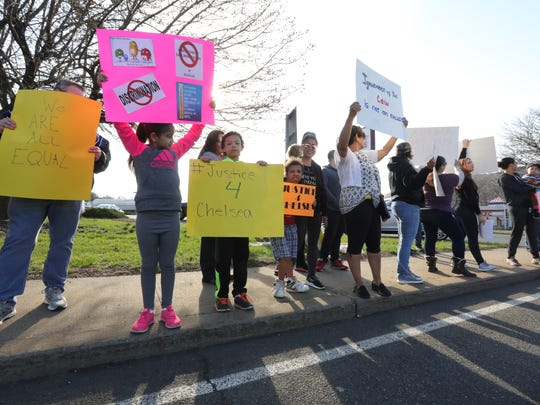 People hold signs during a peaceful protest outside of the Dunkin Donuts in West Haverstraw on Saturday, April 14, 2018.  This Dunkin Donuts is accused of discriminating against a resident who wanted to apply for a job.