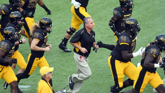 Southern Miss head coach Jay Hopson runs onto the field with his players in a home game against Charlotte at M.M. Roberts Stadium on Saturday.
