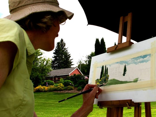 Libby Davidson of Colchester paints a watercolor landscape Sunday in Hinesburg as part of a town-wide garden tour.