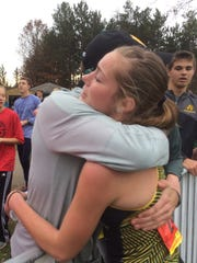 Ashwaubenon sophomore Sage Wagner hugs her father, Todd, after finishing 11th in the Division 1 girls race at the WIAA state cross-country meet in Wisconsin Rapids.