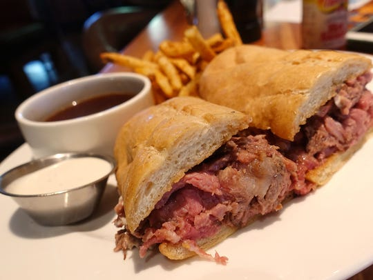 French dip with jus, horseradish sauce and fries at
