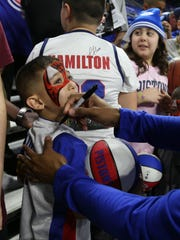 Detroit Pistons guard Ish Smith signs autographs before