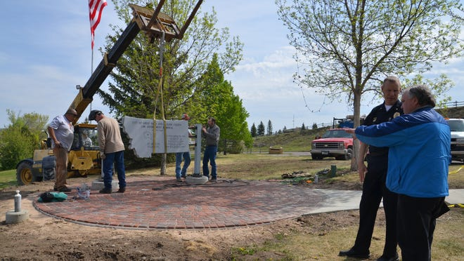 A crew secures the granite component of the Great Falls and Cascade County Law Enforcement Memorial in place Tuesday at the Flag Hill site as Police Chief David Bowen discusses landscaping plans with a crew member.