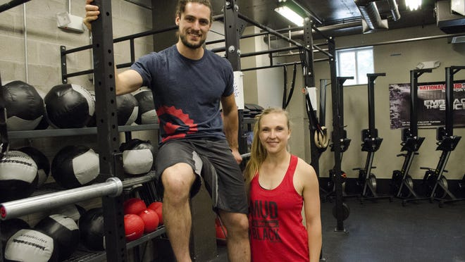 Owners of CrossFit White River, Brandon and Sadie Lowe, pose in their gym.