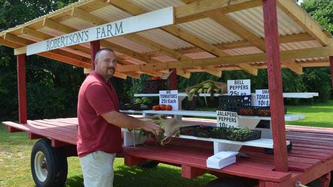 George Robertson Jr. of Newport stocks his family's honor system produce stand. Most items are sold by the piece, and the Robertsons don't mind if you can't afford to pay.